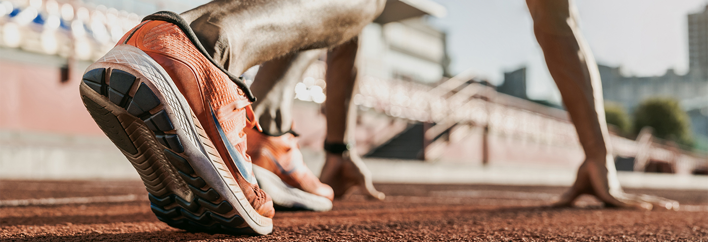 ©InsideCreativeHouse - stock.adobe.com - Close up of male athlete getting ready to start running on track.